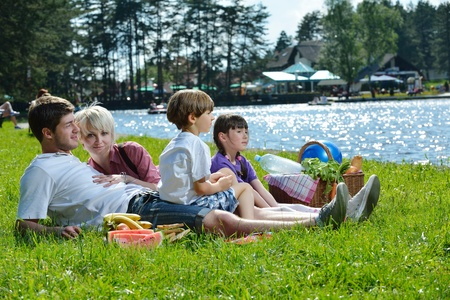 Happy young  family playing together with kids and eat healthy food  in a picnic outdoors photo