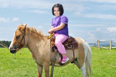 gelukkig kind rit landbouwhuisdieren bruin pony met blauwe hemel in achtergrond en prachtige natuur