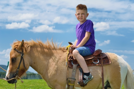pony girl: happy child ride farm animal brown pony with blue sky in background and beautiful nature