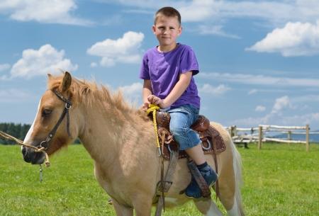 gelukkig kind rit landbouwhuisdieren bruine pony met blauwe hemel op de achtergrond en de mooie natuur