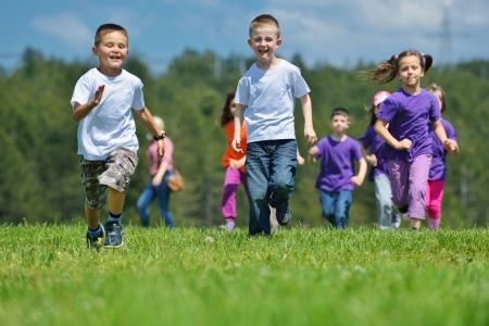 ni�o corriendo: grupo de ni�os felices se divierten en el parque de la naturaleza al aire libre Foto de archivo