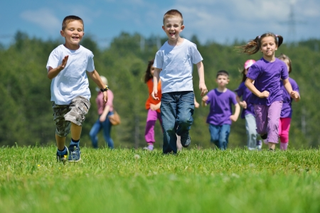 play school: happy kids group have fun in nature outdoors park