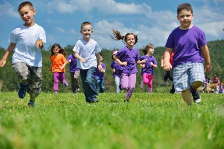 niños felices: grupo de niños felices se divierten en el parque de la naturaleza al aire libre Foto de archivo