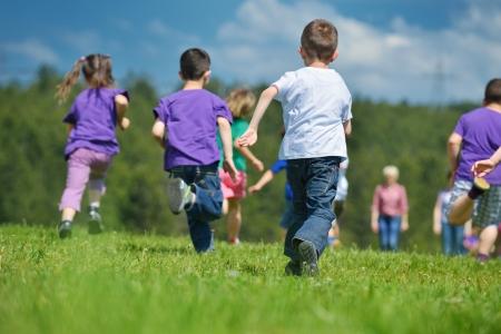 enfant qui court: heureux groupe de jeunes de s'amuser en plein air parc naturel Banque d'images