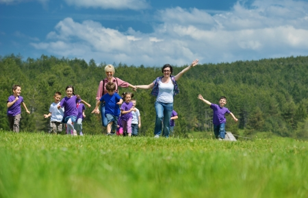 happy preschool  kids group have fun and play game  on outdoor classes in nature photo