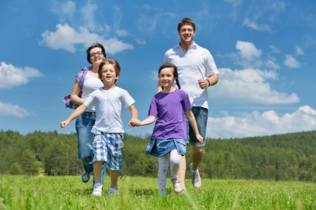 happy young family with their kids have fun and relax outdoors in nature with blue sky in background Stock Photo - 15558080
