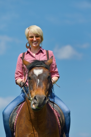 happy woman in sunglasses sitting on horse farm animal outdoors with blue sky in background photo