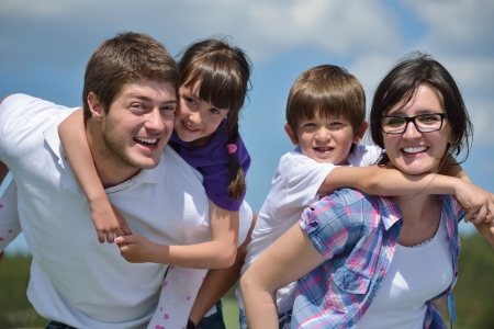 happy family concept: happy young family with their kids have fun and relax outdoors in nature with blue sky in background Stock Photo
