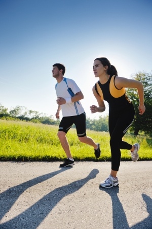 hombres corriendo: Trotar en el parque Pareja joven en la ma�ana. Salud y forma f�sica.