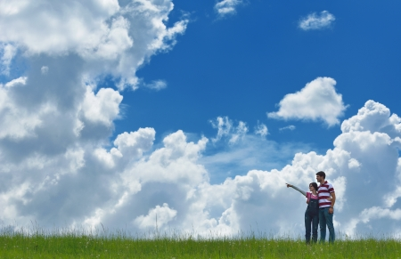 laughing couple: Portrait of romantic young couple in love  smiling together outdoor in nature with blue sky in background