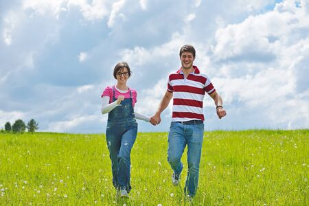 Portrait of romantic young couple in love  smiling together outdoor in nature with blue sky in background photo