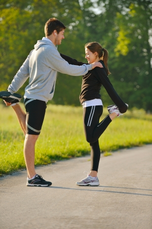 stretching: pareja de la salud joven haciendo ejercicios de estiramiento y relajaci�n calentarse despu�s de trotar y correr en el parque Foto de archivo