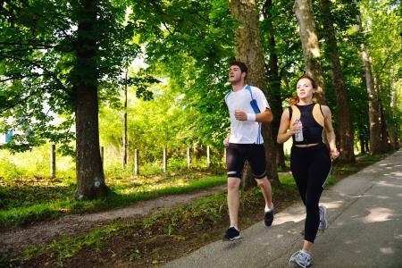 Jong paar joggen in het park 's morgens. Gezondheid en fitness.