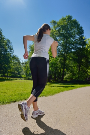 Young beautiful  woman jogging in summer park. Woman in sport outdoors health concept Stock Photo - 14703517
