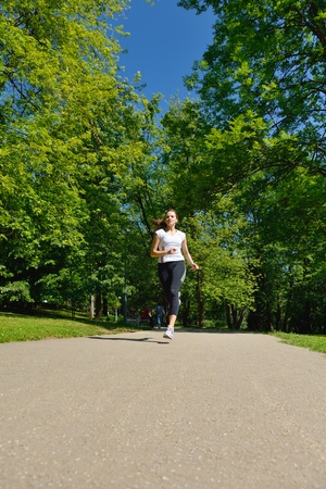 Young beautiful  woman jogging in summer park. Woman in sport outdoors health concept Stock Photo - 14703525
