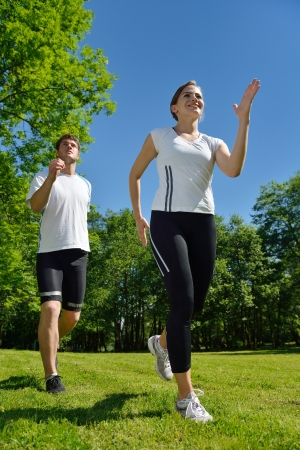 girl jogging: Young couple jogging in park at morning. Health and fitness.