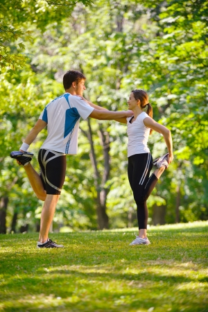 warm up: young health couple doing stretching exercise relaxing and warm up after jogging and running in park