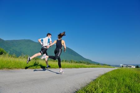 pareja saludable: Joven pareja trotar en el parque en la ma�ana. Salud y estado f�sico. Foto de archivo
