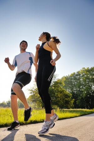 outdoor fitness: Young couple jogging in park at morning. Health and fitness.