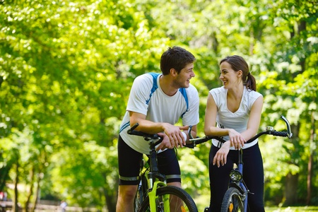 Happy couple riding bicycle outdoors, health lifestyle fun love romance concept photo