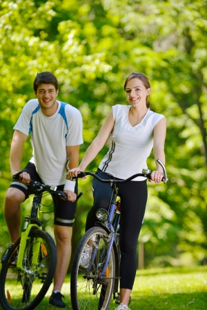 active girl: Happy couple riding bicycle outdoors, health lifestyle fun love romance concept