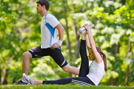 young health couple doing stretching exercise relaxing and warm up after jogging and running in park photo