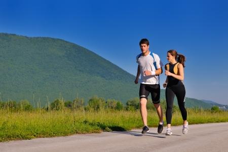 gente corriendo: Trotar en el parque Pareja joven en la ma�ana. Salud y forma f�sica.