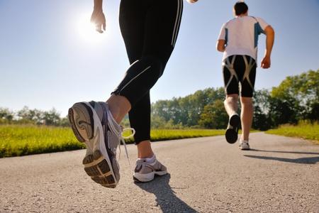 가벼운 흔들림: 아침에 공원에서 조깅하는 젊은 부부. 건강 및 피트니스. 스톡 사진