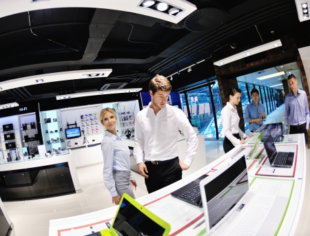 electronics store: Young couple in consumer electronics store looking at latest laptop, television and photo camera