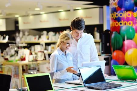 Junges Paar in der Unterhaltungselektronik Blick auf neuesten Laptop, Fernsehen und Foto-Kamera