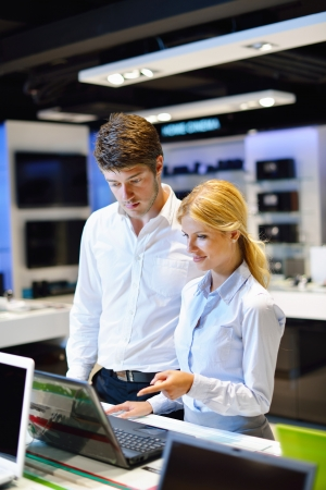 Young couple in consumer electronics store looking at latest laptop, television and photo camera Stock Photo - 15275757