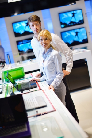 Young couple in consumer electronics store looking at latest laptop, television and photo camera Stock Photo - 15273032