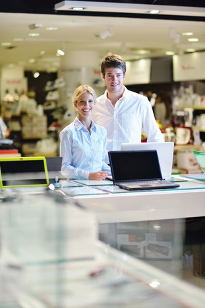 Young couple in consumer electronics store looking at latest laptop, television and photo camera Stock Photo - 15272999
