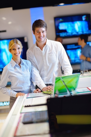 Young couple in consumer electronics store looking at latest laptop, television and photo camera Stock Photo - 15273016