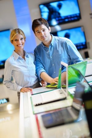 Young couple in consumer electronics store looking at latest laptop, television and photo camera Stock Photo - 15273038
