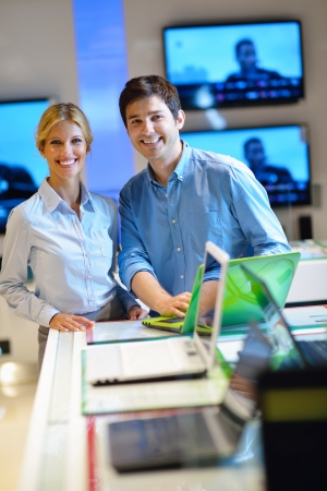 Young couple in consumer electronics store looking at latest laptop, television and photo camera Stock Photo - 15273043