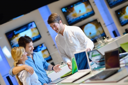 Young couple in consumer electronics store looking at latest laptop, television and photo camera Stock Photo - 15273036