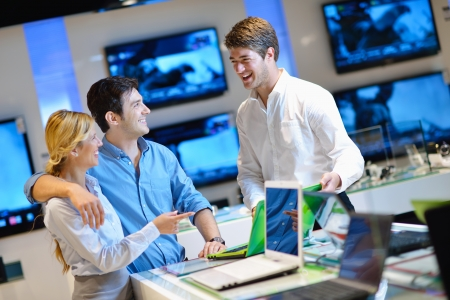 magasin: Jeune couple dans un magasin d'�lectronique regardant la cam�ra dernier ordinateur portable, t�l�vision et photo Banque d'images