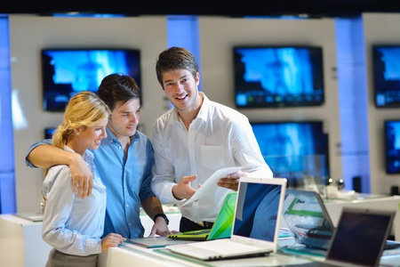 electronic store: Young couple in consumer electronics store looking at latest laptop, television and photo camera