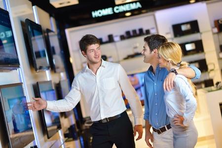 consommateurs: Jeune couple dans un magasin d'�lectronique regardant la cam�ra dernier ordinateur portable, t�l�vision et photo Banque d'images