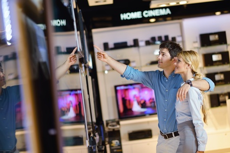 Young couple in consumer electronics store looking at latest laptop, television and photo camera Stock Photo - 15273046