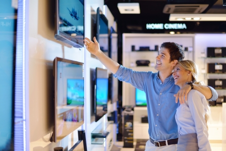 consumer electronics: Young couple in consumer electronics store looking at latest laptop, television and photo camera