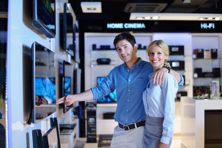 electronics store: Giovane coppia in negozio di elettronica di consumo, cercando in ultimo laptop, televisione e macchina fotografica Archivio Fotografico