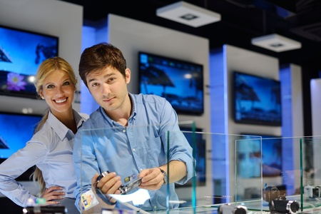 Young couple in consumer electronics store looking at latest laptop, television and photo camera Stock Photo - 15275772