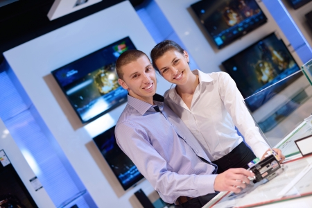 Young couple in consumer electronics store looking at latest laptop, television and photo camera to buy Stock Photo - 15273144