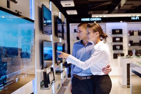 electronics store: Giovane coppia in negozio di elettronica di consumo, cercando in ultima fotocamera portatile, televisione e foto da acquistare