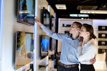 consommateurs: Jeune couple dans un magasin d'�lectronique regardant la cam�ra dernier ordinateur portable, la t�l�vision et la photo pour acheter
