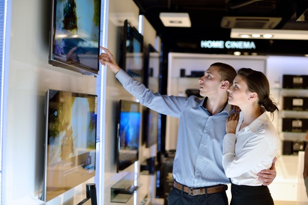 Young couple in consumer electronics store looking at latest laptop, television and photo camera to buy Stock Photo - 15275762