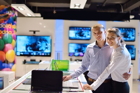 Young couple in consumer electronics store looking at latest laptop, television and photo camera to buy Stock Photo - 14862486