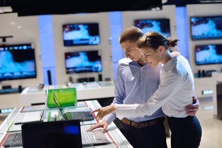 Young couple in consumer electronics store looking at latest laptop, television and photo camera to buy photo
